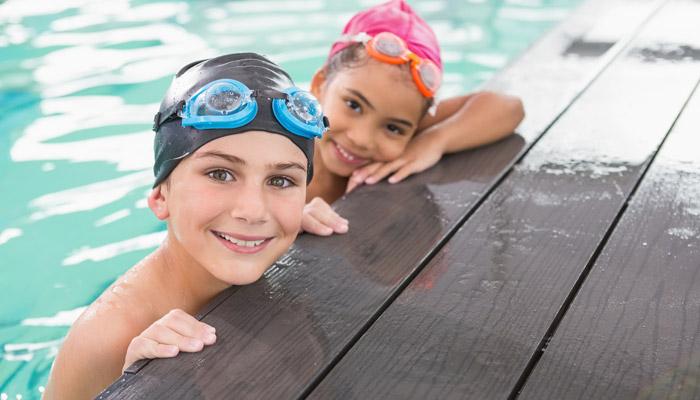 Дети в плавательных шапочках и с защитными очками в бассейне
