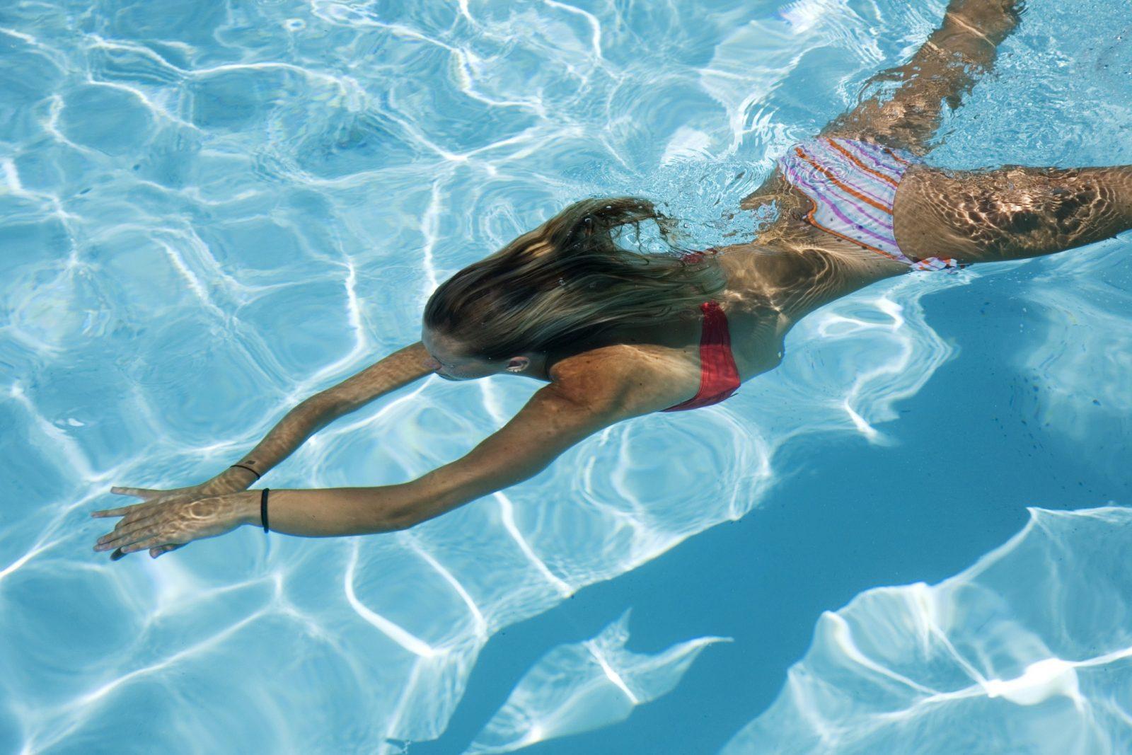Девушка плывет под водой в раздельном купальнике